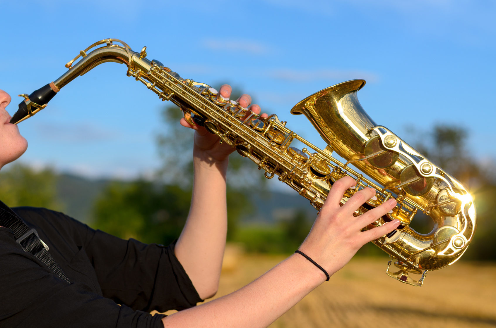 Side close up view of a young woman playing a tenor saxophone outdoors in the countryside raising the instrument in the air against a blue sky